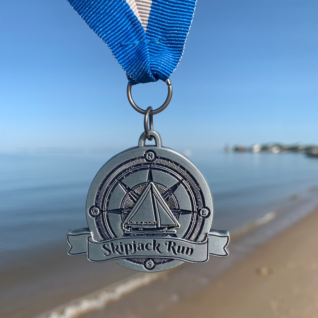 Small Skipjack Run medal hanging with blurred beach in the background.