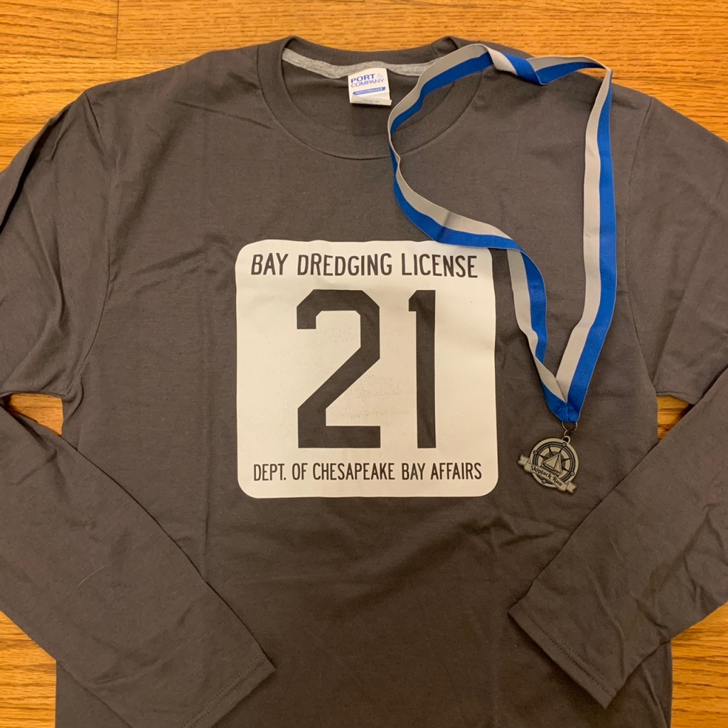 """Gray long-sleeved shirt with a white rounded square that says """"Bay Dredging License / 21 in large font / Dept of Chesapeake Bay Affairs,"""" along with small medal."""